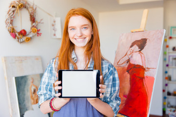 Beautiful happy woman holding blank screen tablet in art workshop