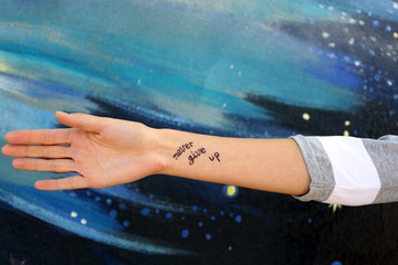 Female hand with tattoo on wall background