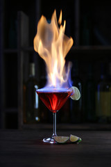 Burning cocktail and lime on table in a bar