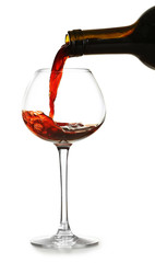 Red wine pouring in glass, isolated on white