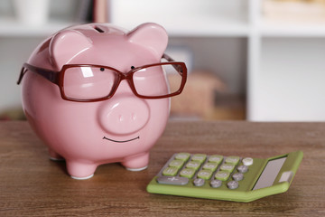 Piggy bank in glasses with calculator on home or office background