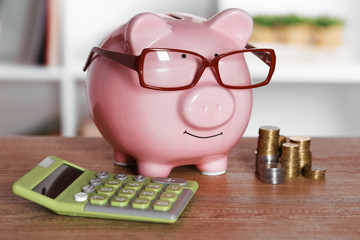 Piggy bank in glasses with calculator and coins on home or office background