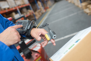Man in warehouse wearing handheld scanner and computer