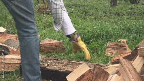 lumberjack cutting firewood with axe in backyard