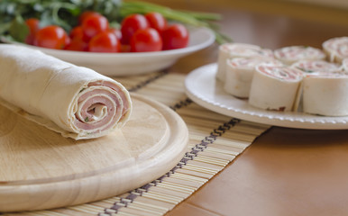 Roll with ham on a wooden board