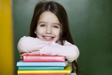 Little girl with books at school