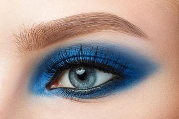 Close-up of woman blue eye with beautiful blue smokey eyes makeu