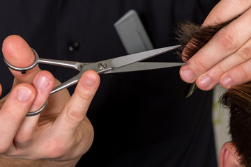 men's hair cutting with scissors in a beauty salon