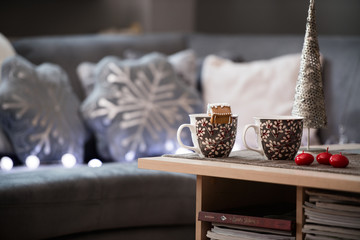 Winter scene. Living room, mugs, candle on the table.
