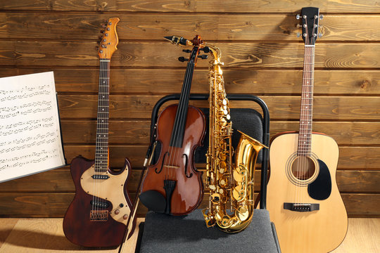 Musical instruments on a chair and note holder against wooden background