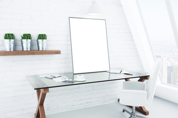 Blank white picture frame on glassy table in modern white style