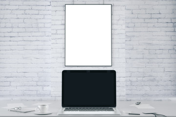 Blank picture frame on white brick wall and blank black laptop s