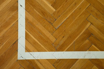 White corner. Worn out wooden floor of sports hall with marking lines