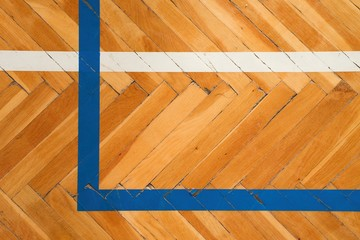 Blue white lines. Worn out wooden floor of sports hall with colorful marking lines.