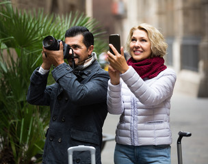 tourists sightseeing and making photo on camera and smartphone