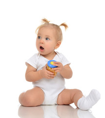 Baby girl sitting and holding jar of child mash puree food