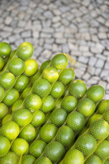 Fresh limes stacked in rows of sacks at the farmers market in General Osorio Plaza in Ipanema, Rio de Janeiro, Brazil