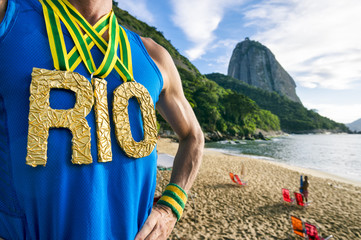 Athlete wearing gold RIO medals standing outdoors in front of Sugarloaf Mountain in Rio de Janeiro, Brazil during golden morning sunrise