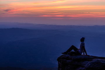 Man sitting on mountain peak at sunset with mountains background.