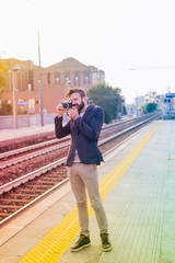 young handsome caucasian brown hair bearded man in a railway sta