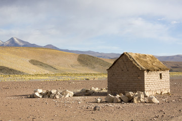 Adobe house on Bolivian Altiplano with Andean mountain, Bolivia