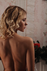 Sensual blonde woman posing in black sexy lingerie near fireplace