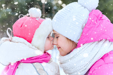 Outdoor portrait of mother and child. Daughter kissing her mother in winter park