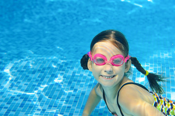 Child swims in pool underwater, happy active girl in goggles has fun under water