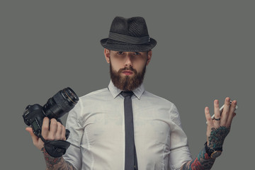 A man with tattooes on arms holding dslr photo camera.
