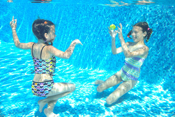 Children swim in pool or sea underwater, happy active girls have fun under water