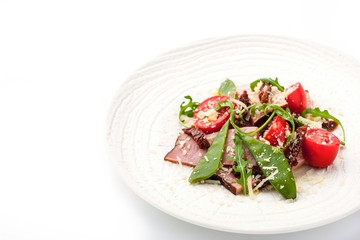 Smoked ham and arugula salad on the white plate horizontal