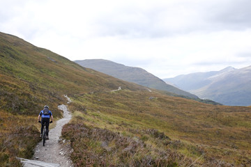 Rear view of man mountain biking, Highlands, Scotland