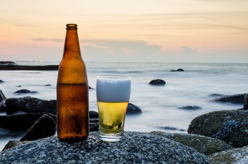 Glass of beer and bottle of beer on a rock on the beach