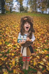 Young girl dressed as owl with owl toy shouting