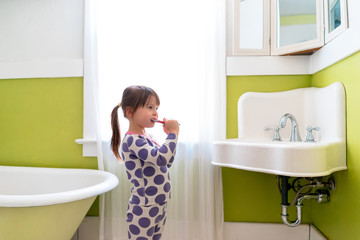 Side view of Girl brushing teeth in bathroom