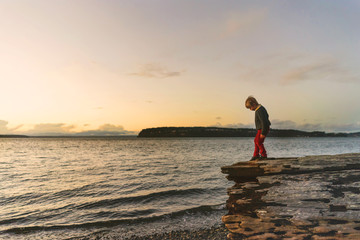 Boy standing on a log at the beach