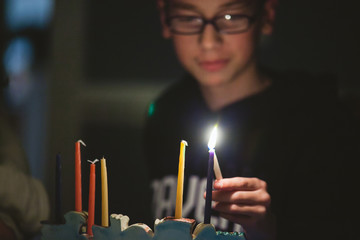 Teenage boy lighting Menorah during Hanukkah