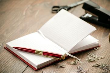 Notepad, pen, staples, stapler and scissors on the table