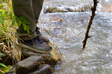 Close up of male hiking boots on hiker  walking crossing river creek