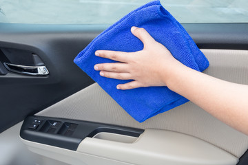 Concept of Hand cleaning interior car door panel with microfiber