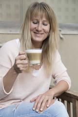 glückliche Frau mit Milchkaffee
