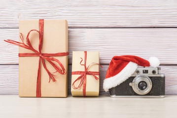 Vintage camera in santa hat with gift boxes over wooden backgrou