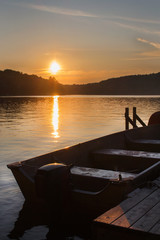 Landscape of a northern lake at sunset wooden deck Canadian cottage with motor boat