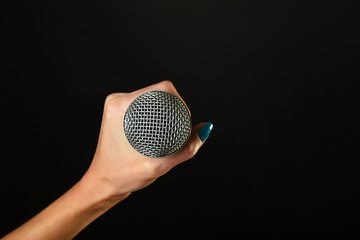 Woman hand with microphone isolated on black