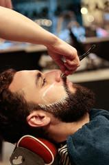 Female hairdresser cutting beard to a boy
