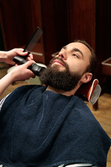 Man shaving his beard at the hairdresser