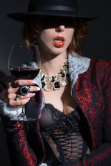 Wall Mural - Fashionably dressed girl in a jacket, with a glass of red wine