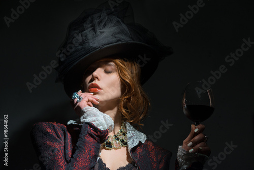 Wall mural A woman in a hat with a glass of red wine
