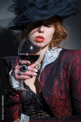 Wall mural Girl with a glass of red wine