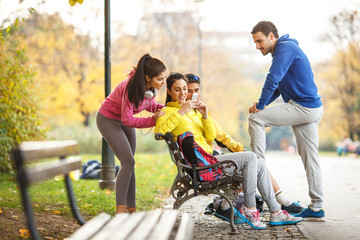 Young runners sitting on bench and relaxing after jogging.